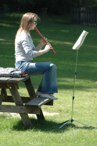 Photo of girl playing recorder outside in sunshine